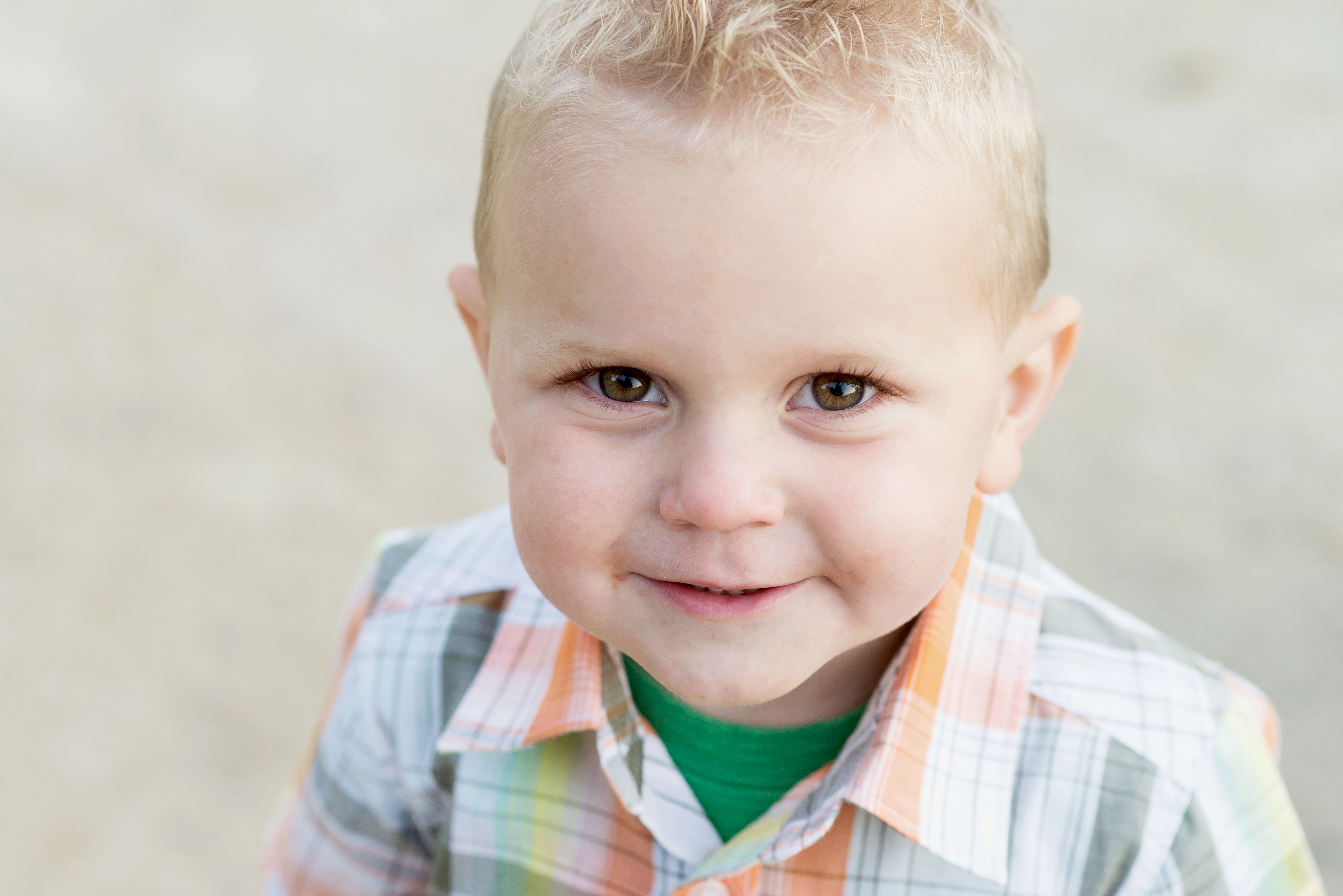 A cute little boy in a plaid shirt smiles up at the camera