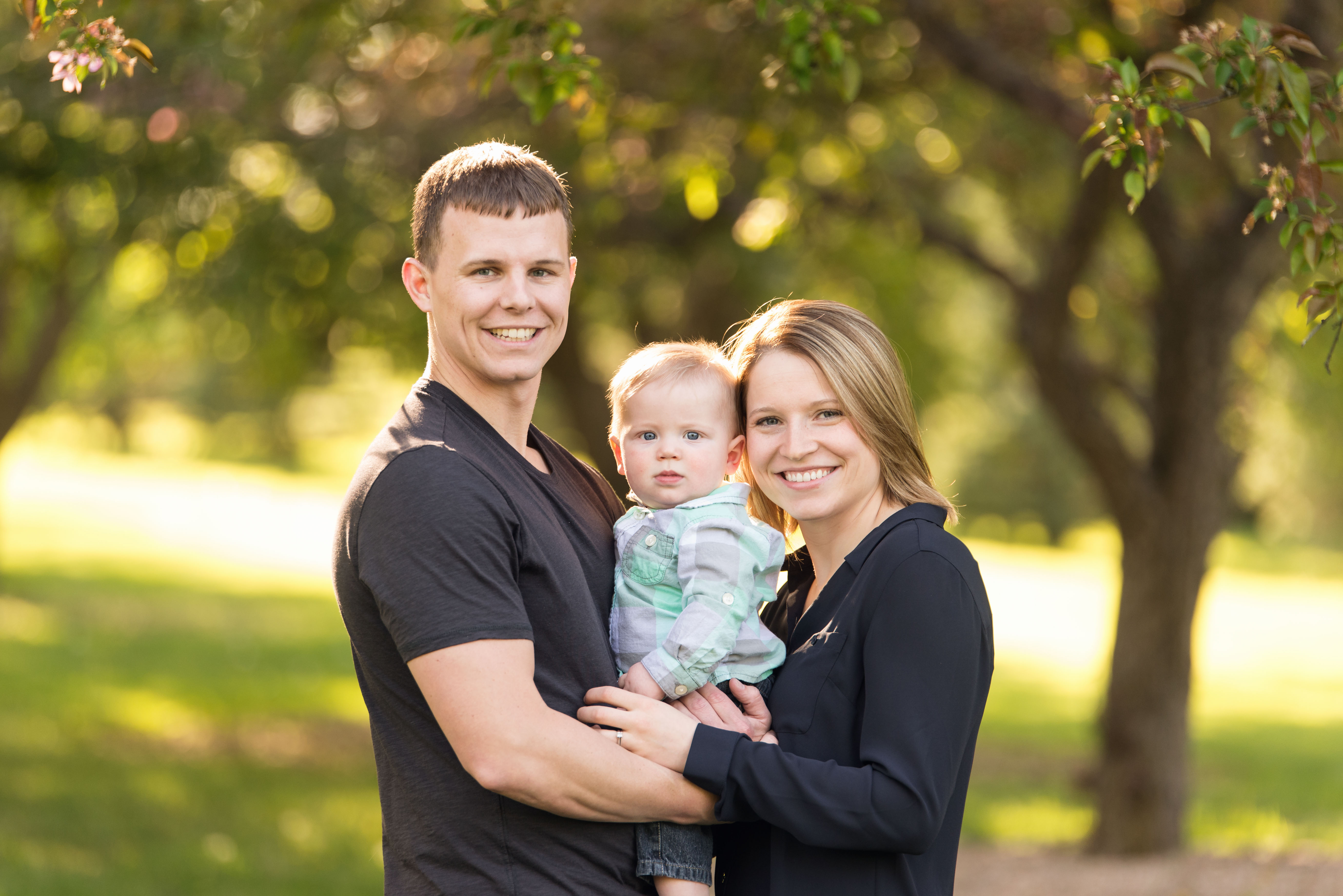 A family with a 6 month old baby boy smile in Cedar Rapids
