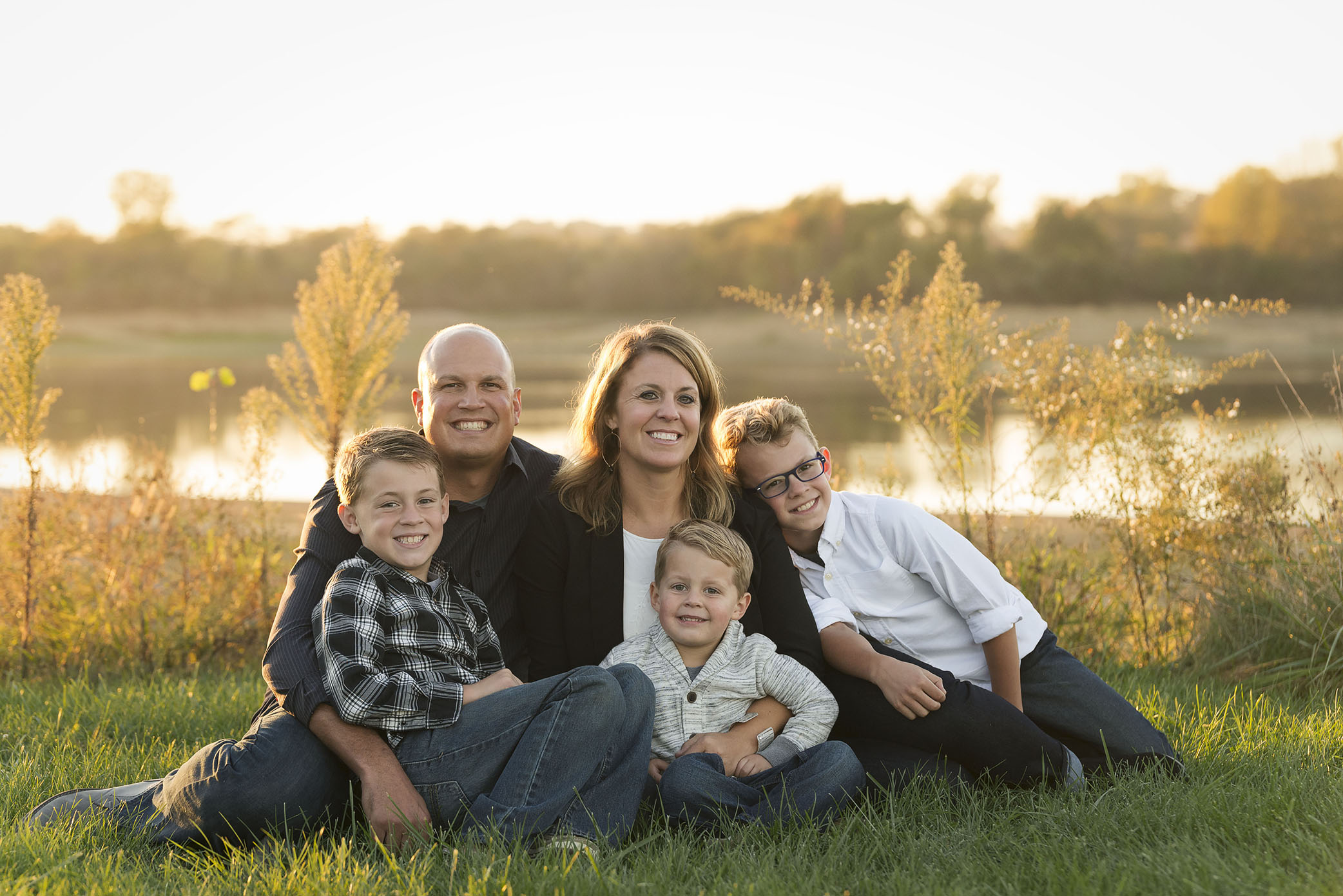 a family smiles for a photography session in Cedar Rapids