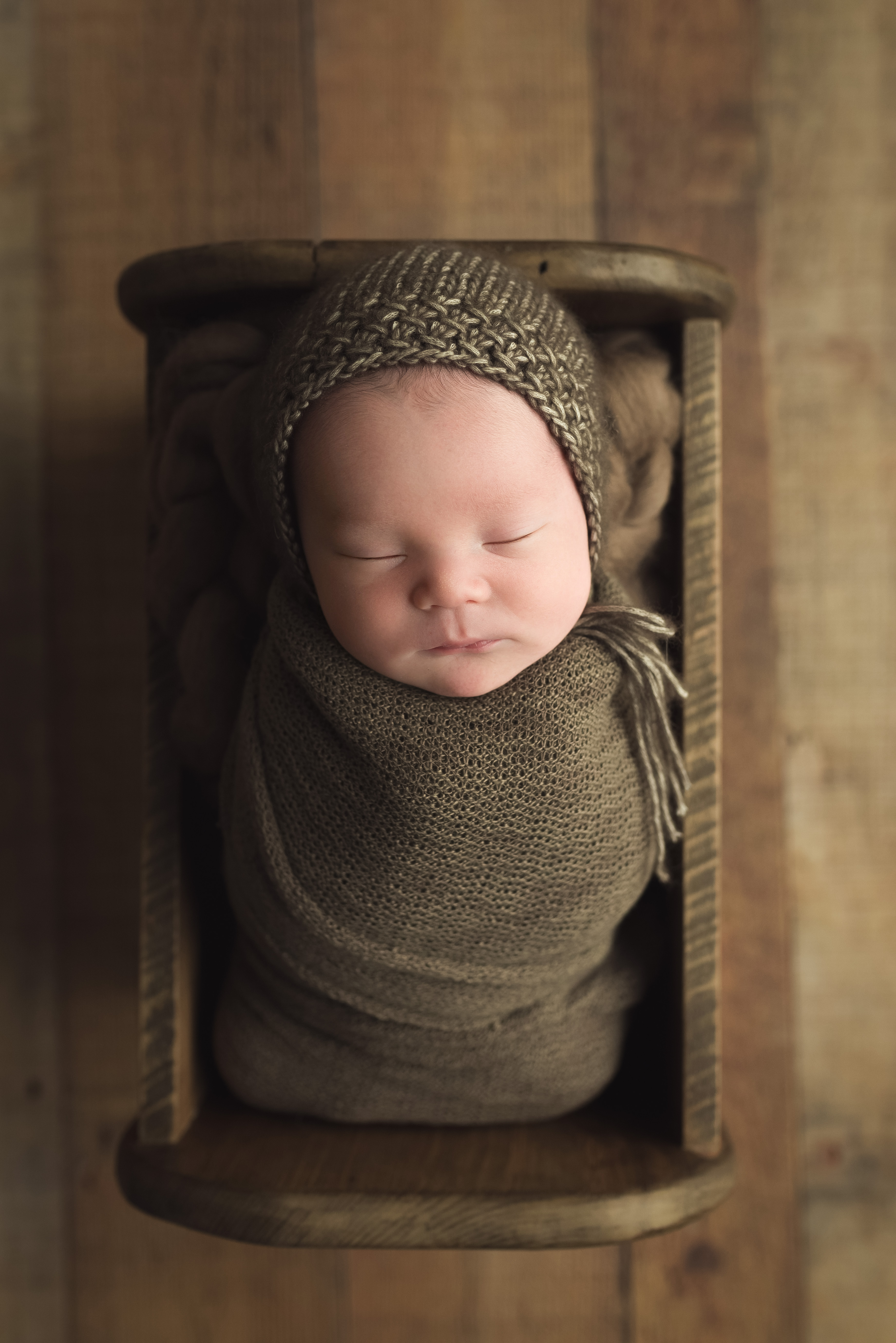A newborn baby boy sleeps during his photography session in Cedar Rapids