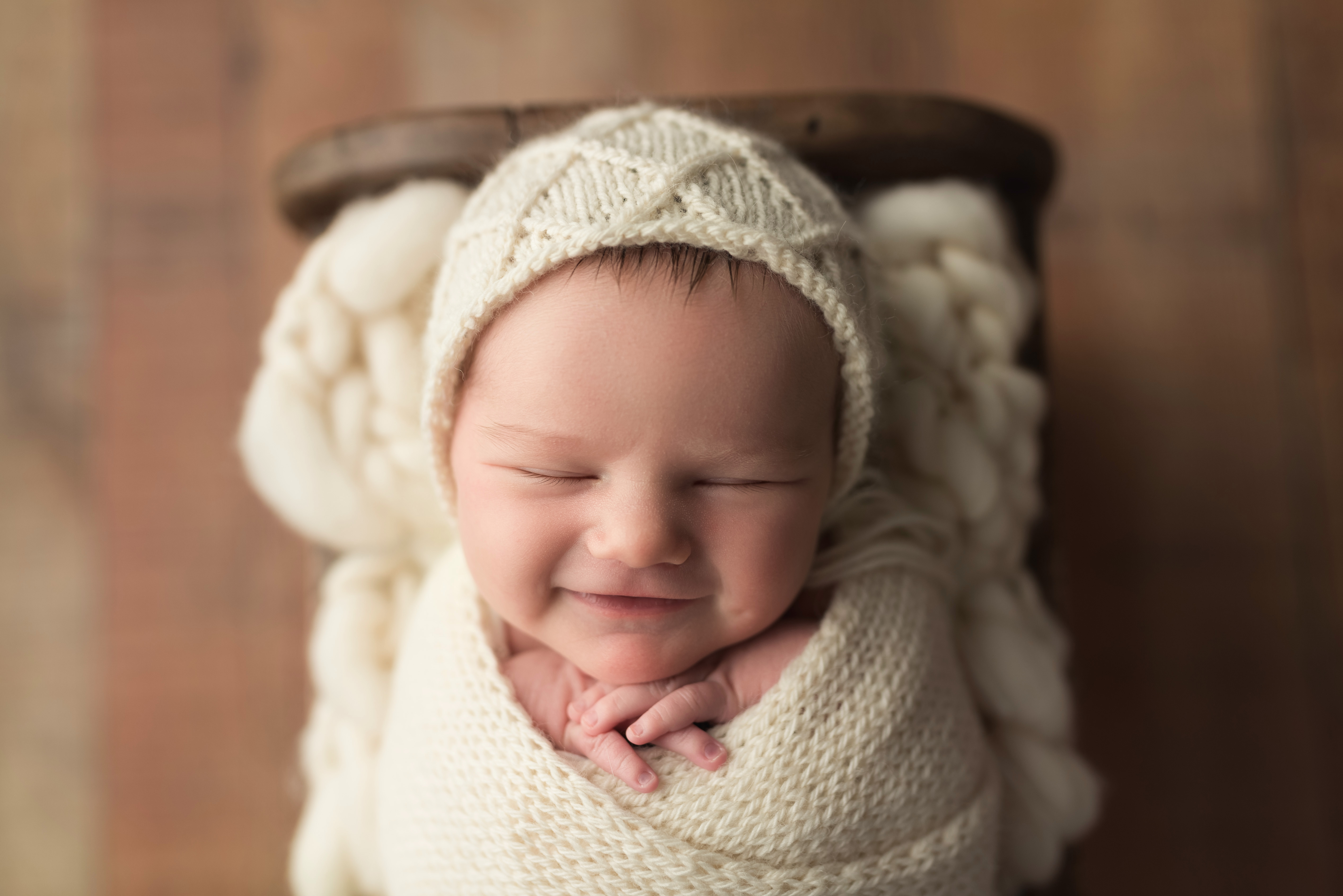 A newborn baby smiles during her photography session in Cedar Rapids