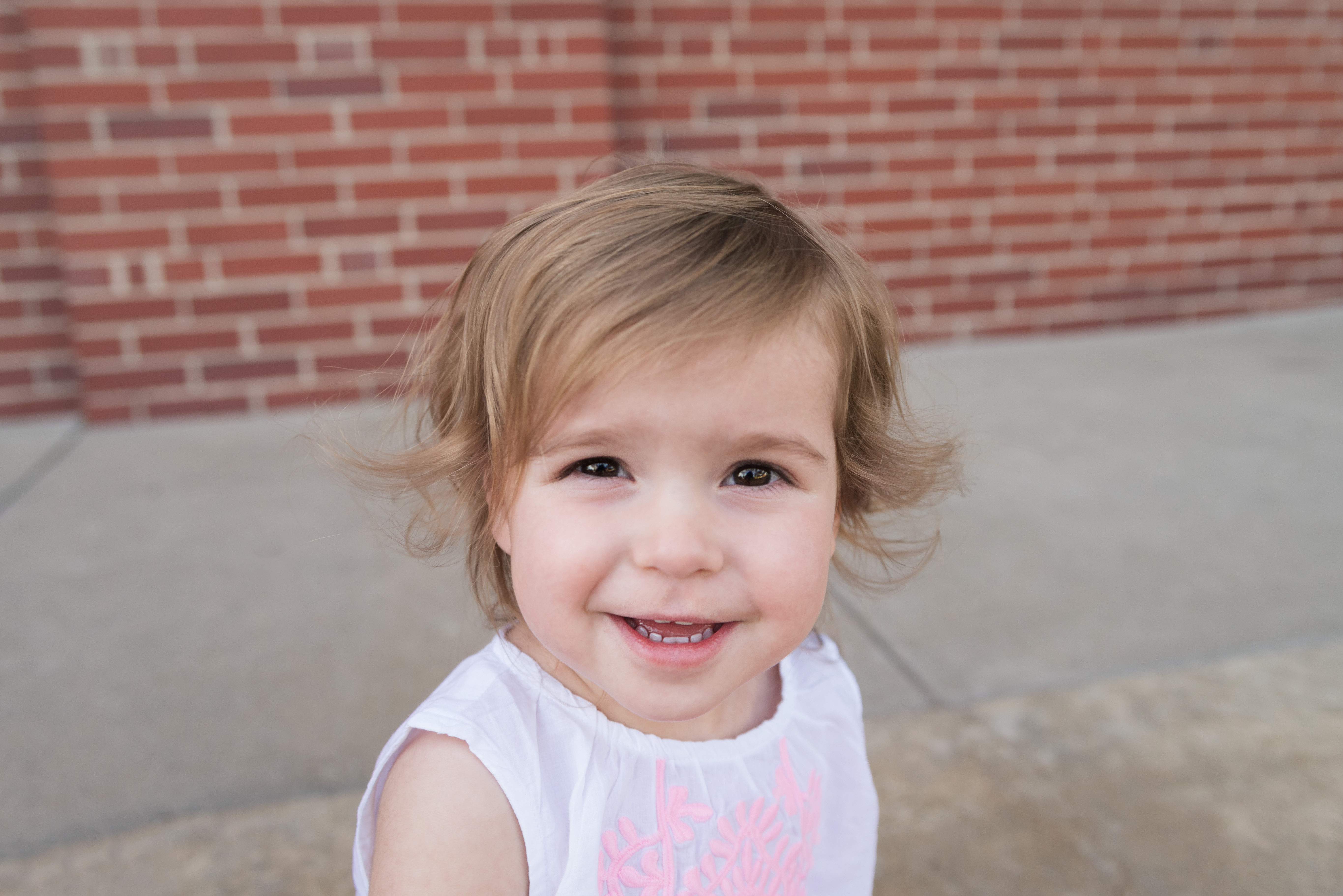 A child smiles for a photo in the NewBo area of Cedar Rapids during her photography session
