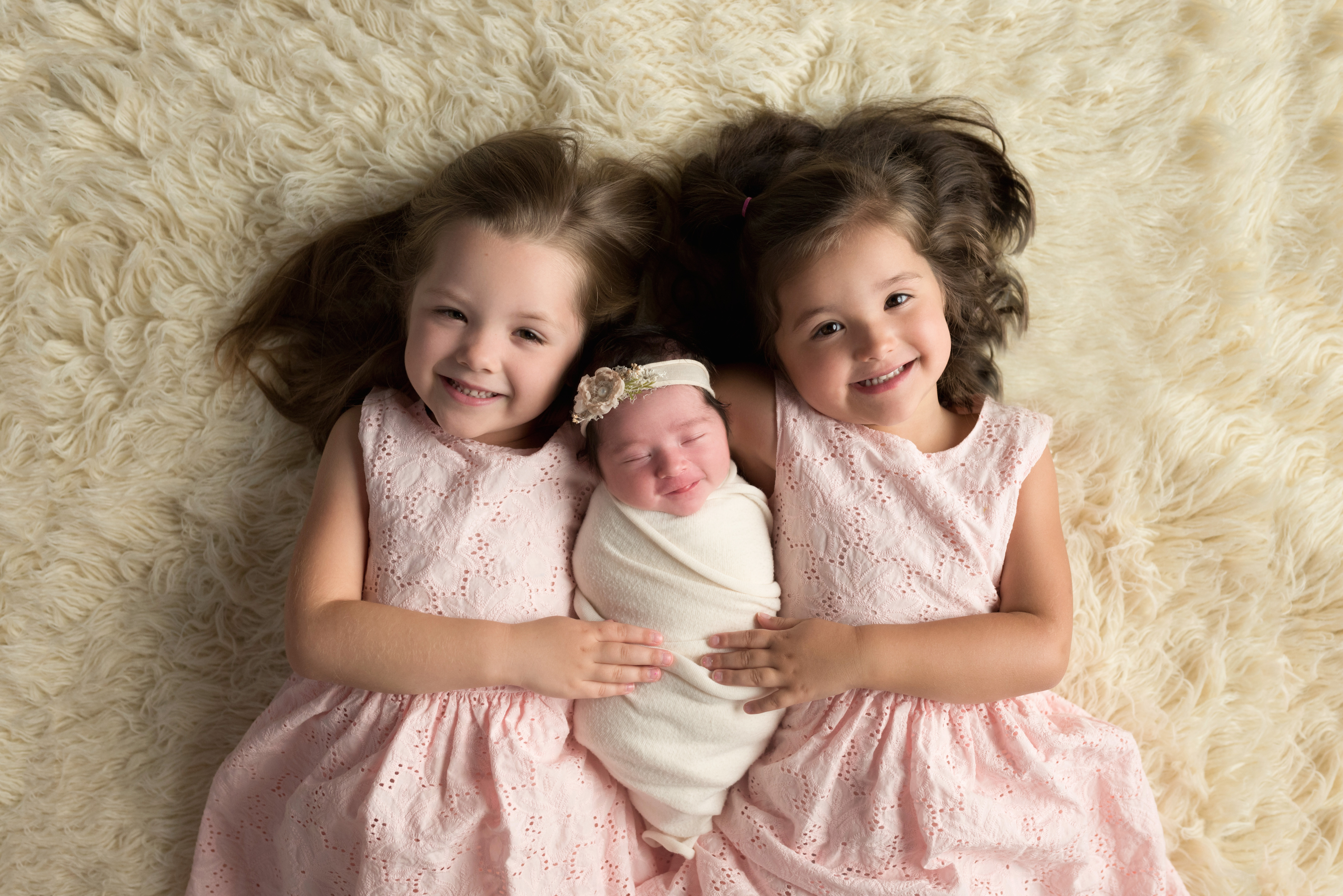Three sisters smile during a newborn photography session in Cedar Rapids