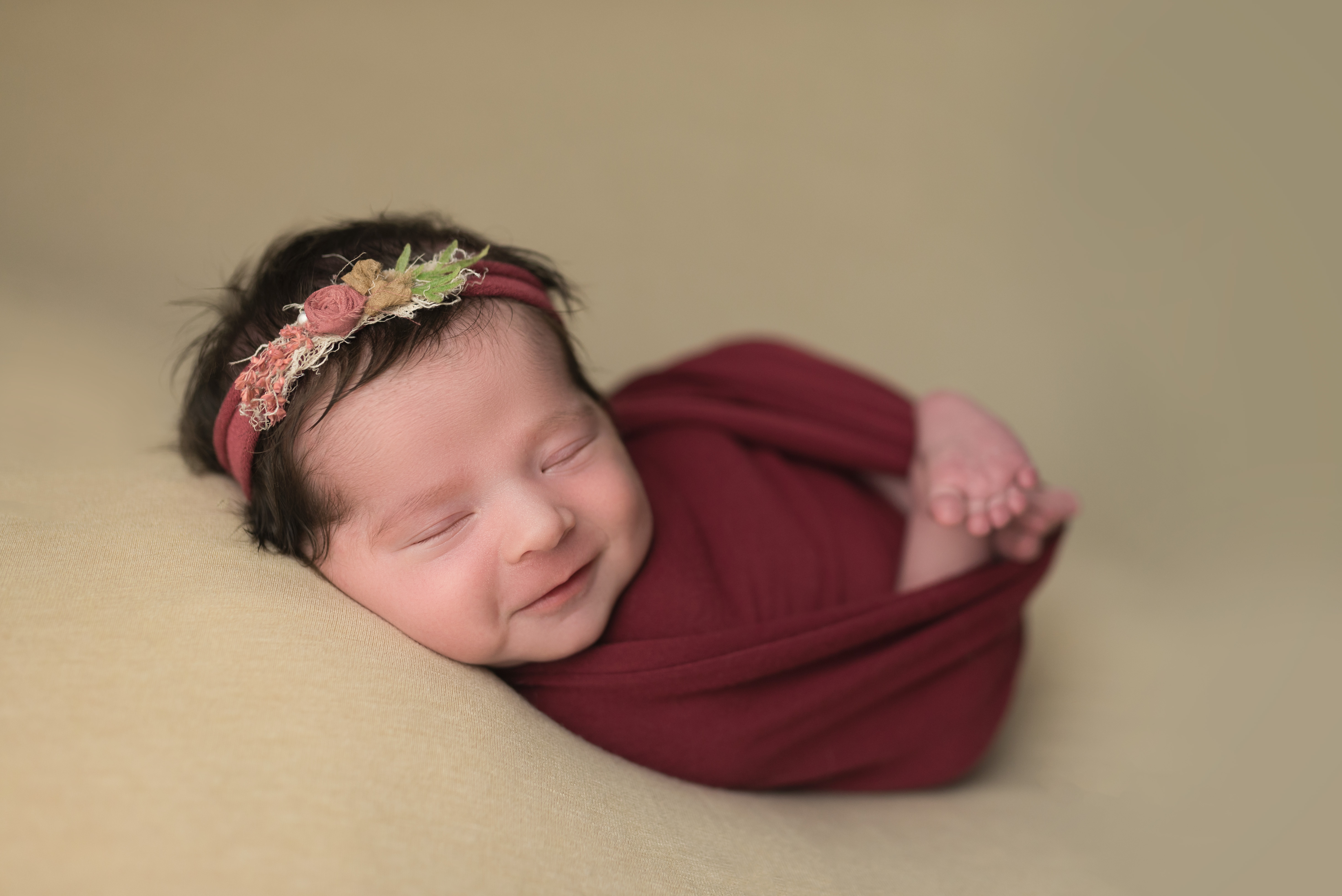 A sweet baby girl smiles during her newborn session in Cedar Rapids