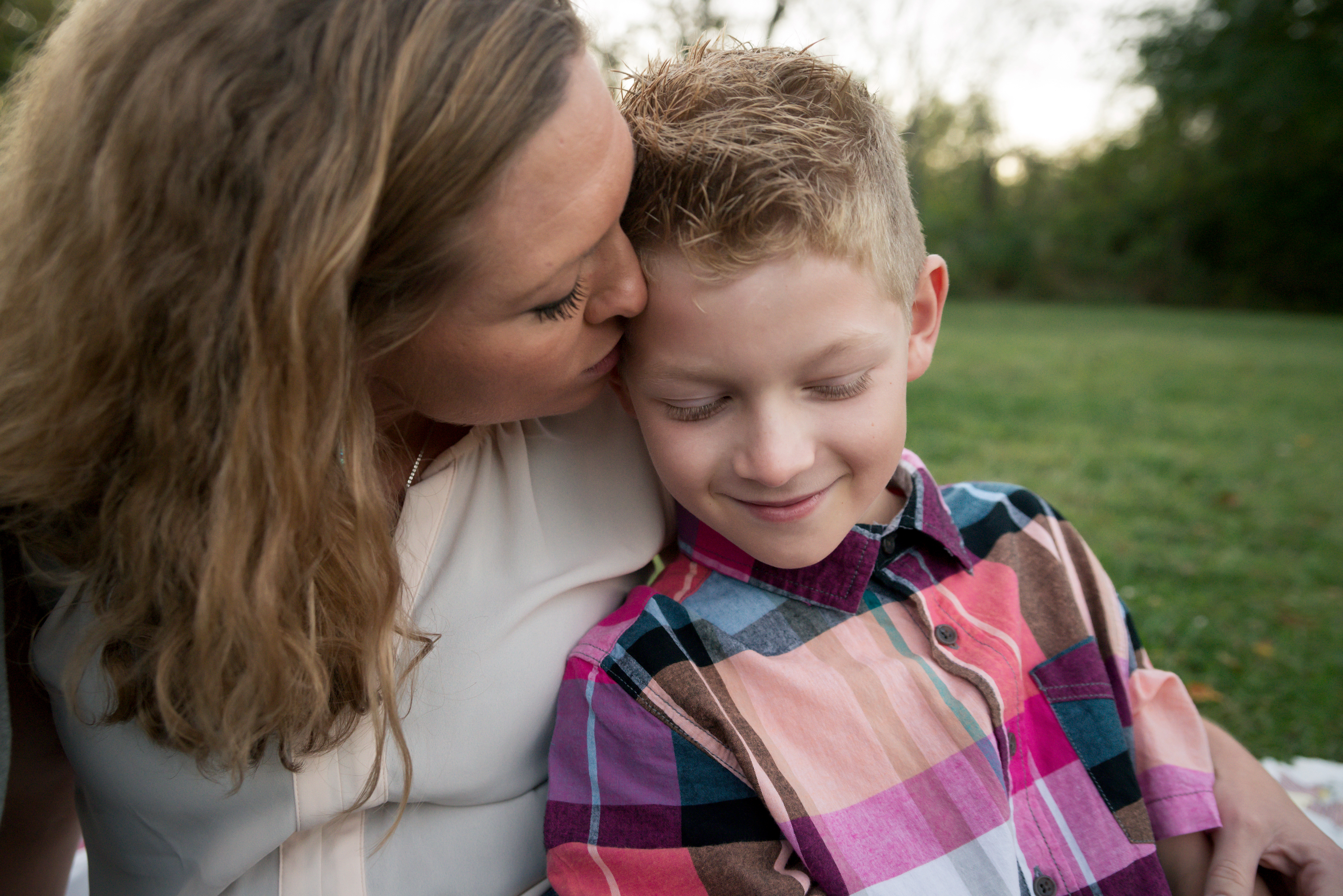 A boy smiles and snuggles his mom during a family photography session in Cedar Rapids