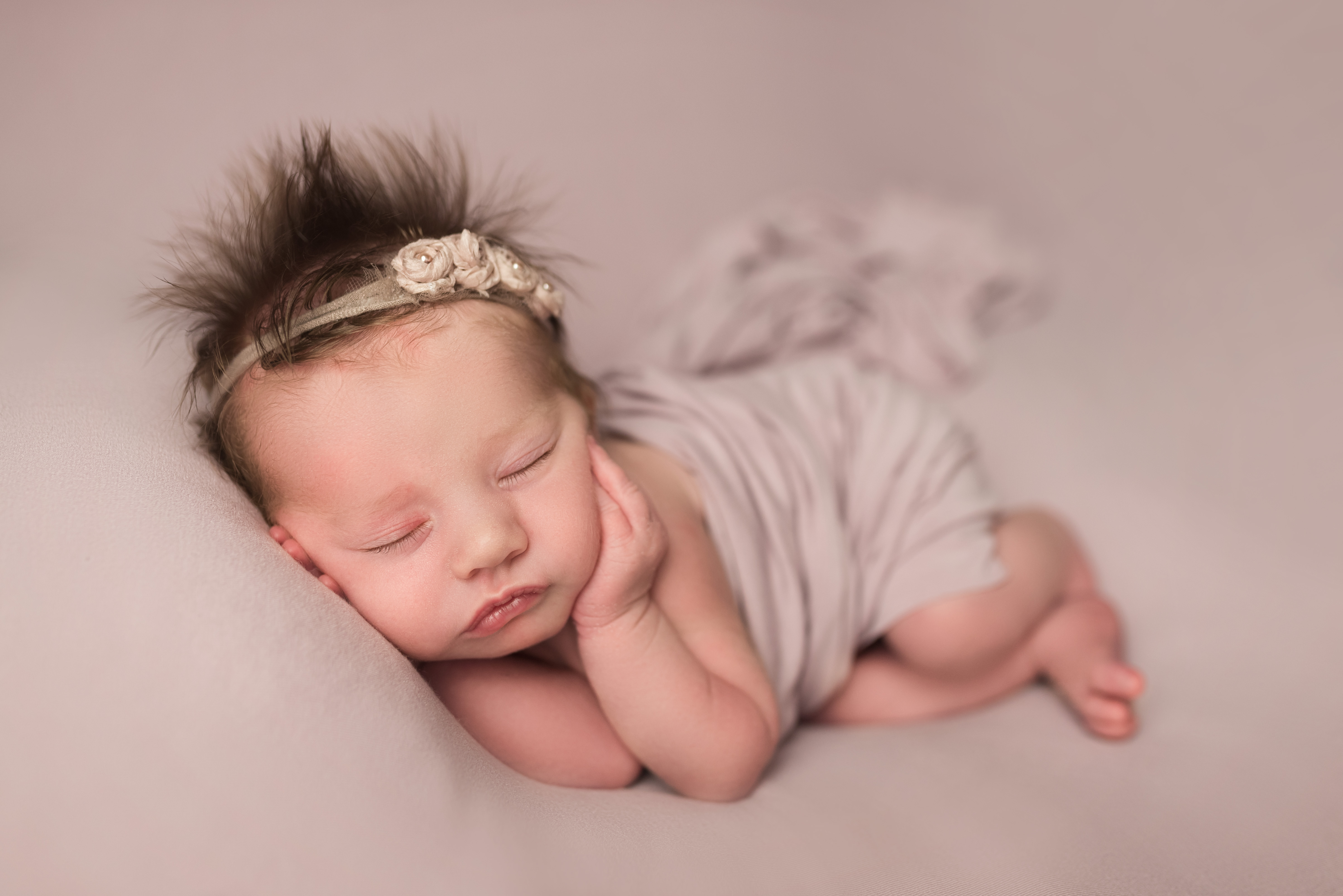 A baby girl in purple sleeps during her newborn photography session in Cedar Rapids