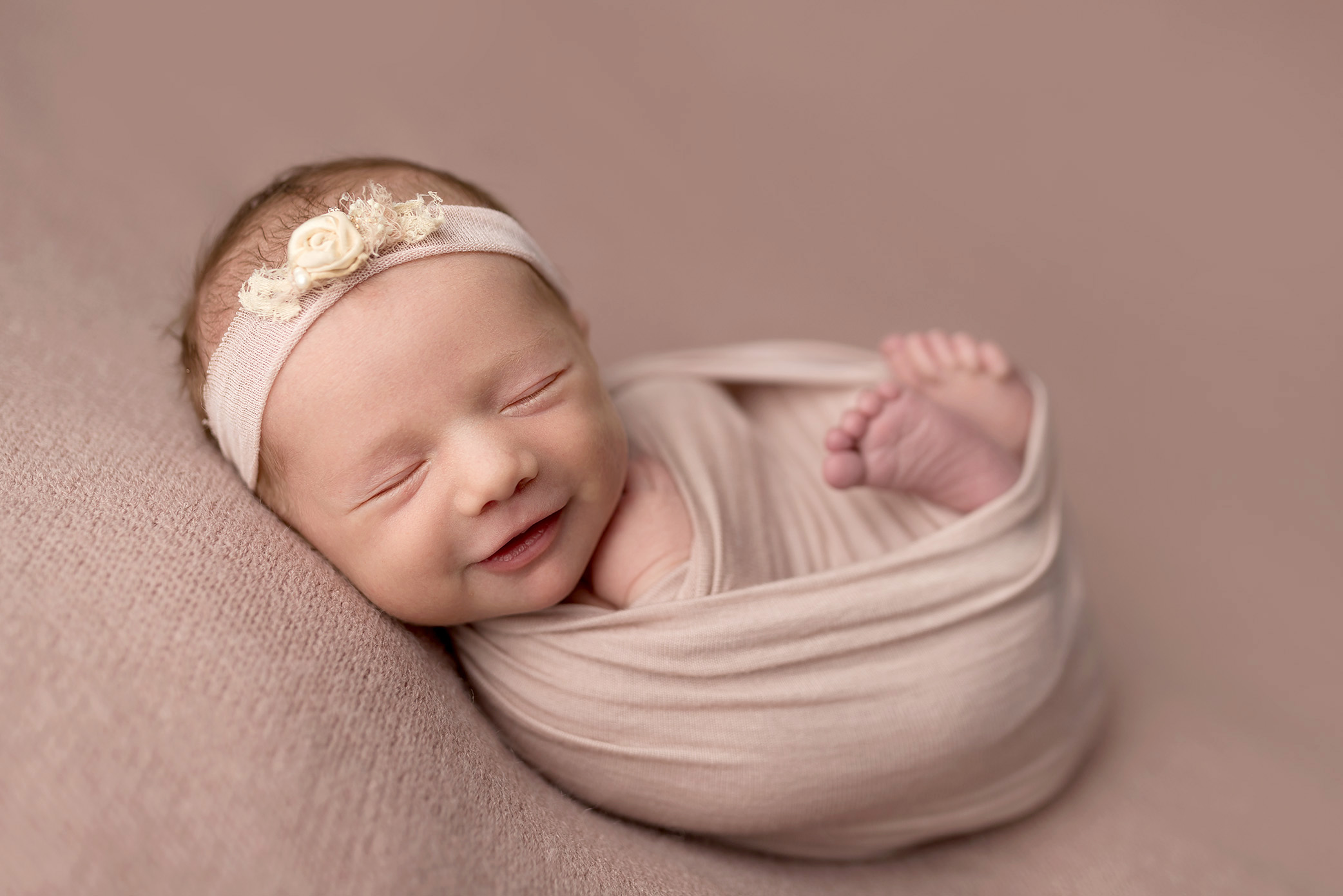 A sweet baby girl smiles during her Cedar Rapids newborn photographer session