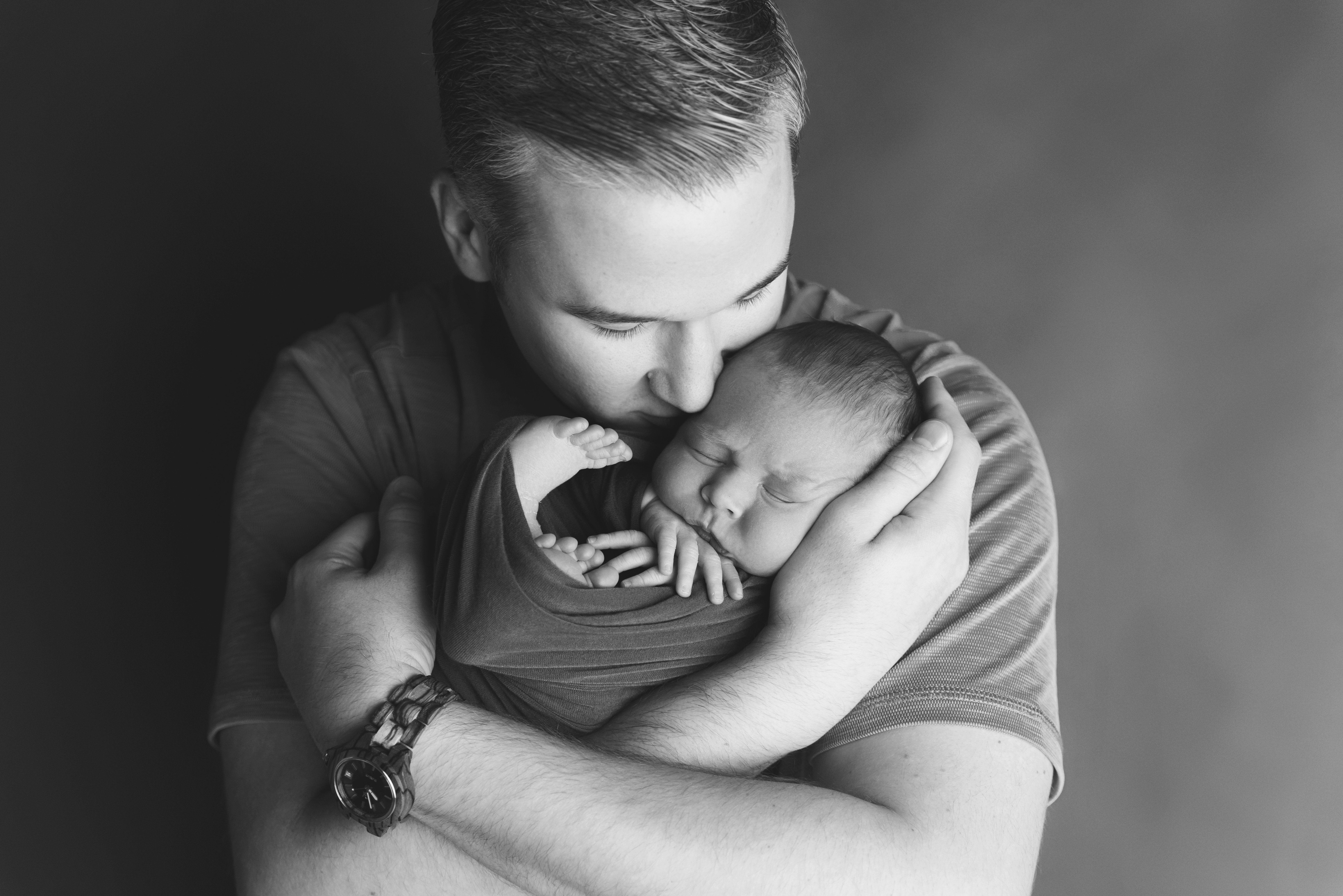 A newborn baby sleeps while being held by his daddy during his photography session in Cedar Rapids