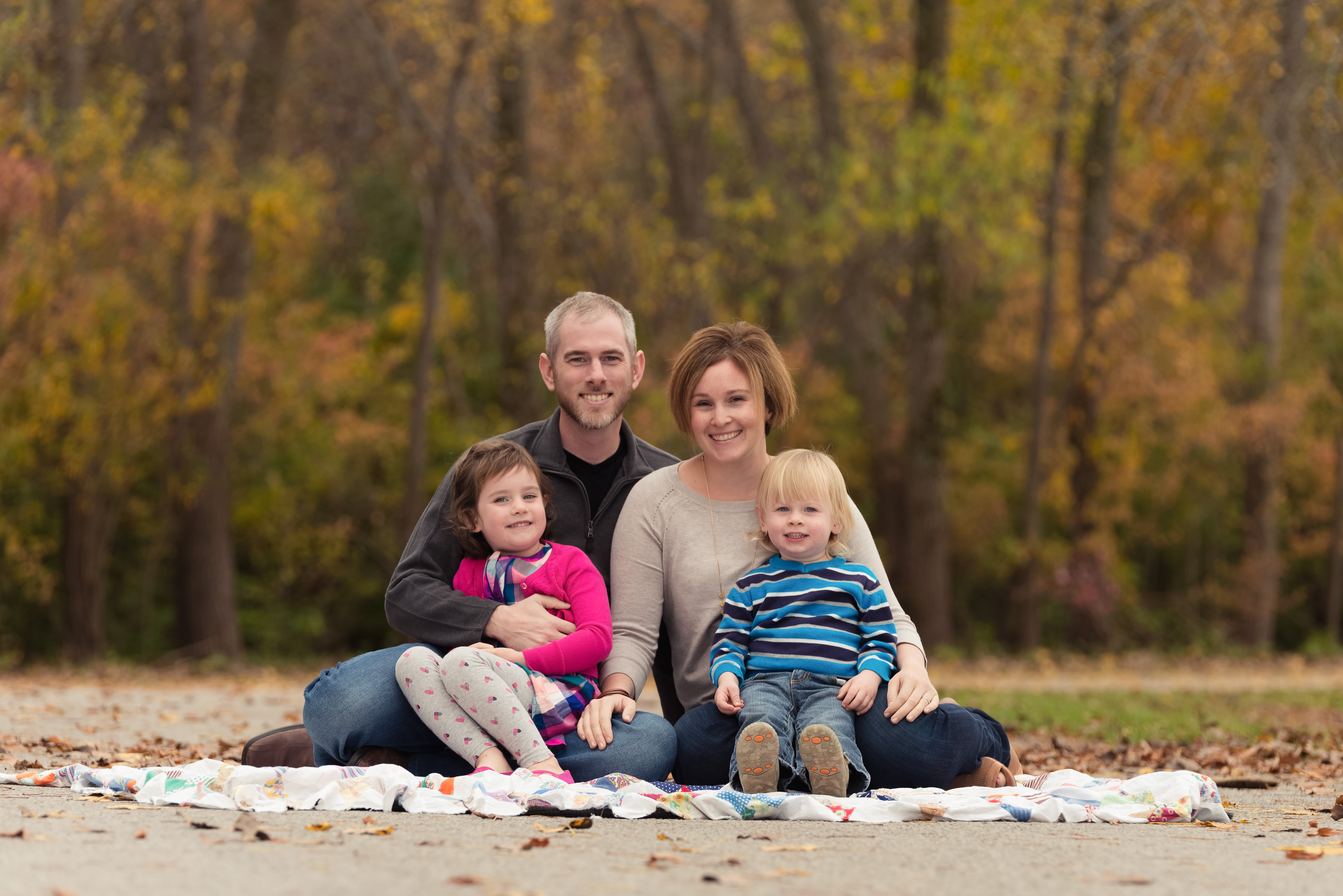 A family smiles during their photography session in Cedar Rapids