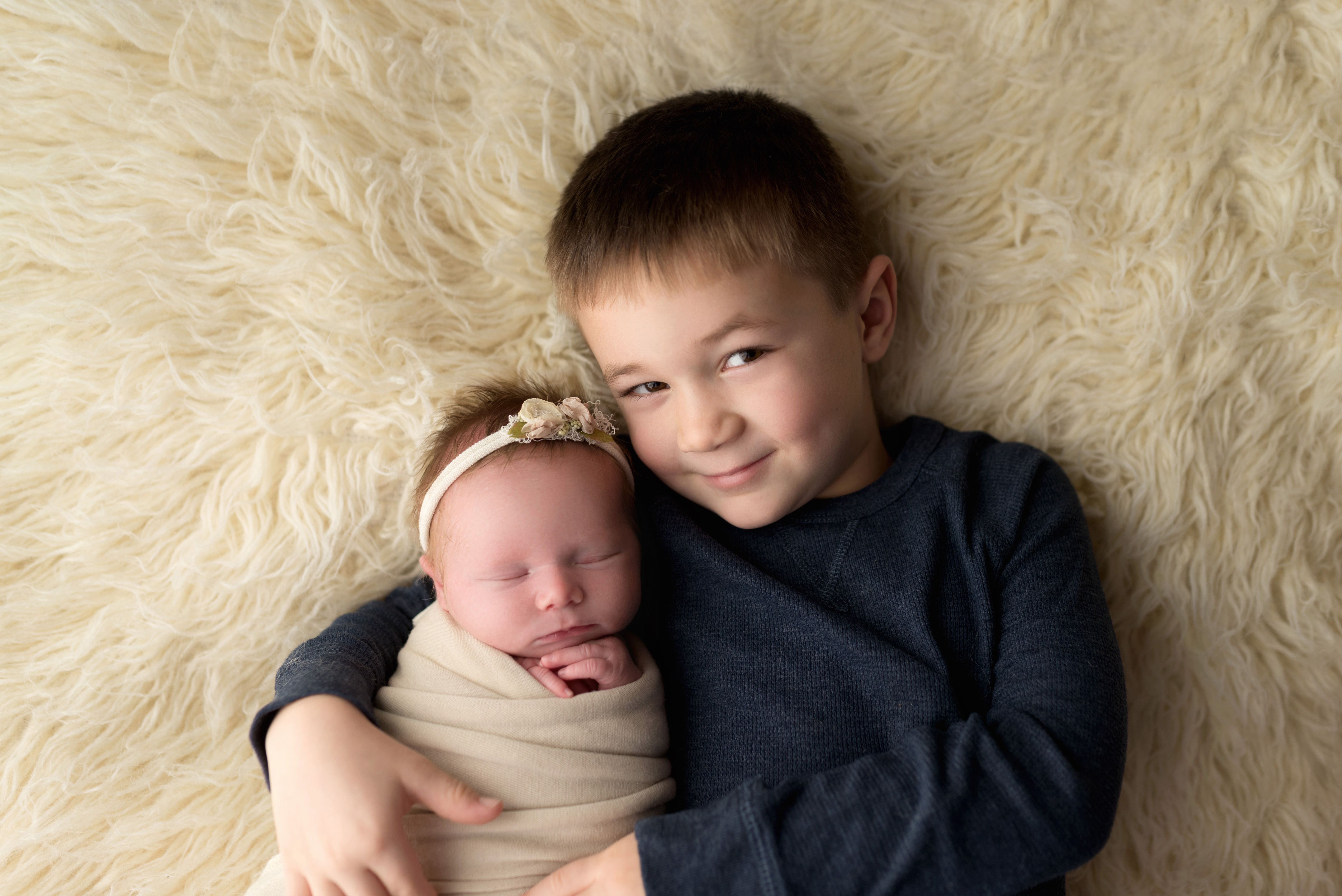 A sweet big brother snuggles his newborn baby sister during her session with a Cedar Rapids photographer